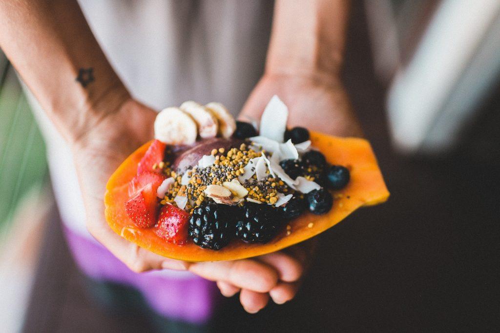 Holding papaya,berries, blackberries, strawberries, fruit dessert